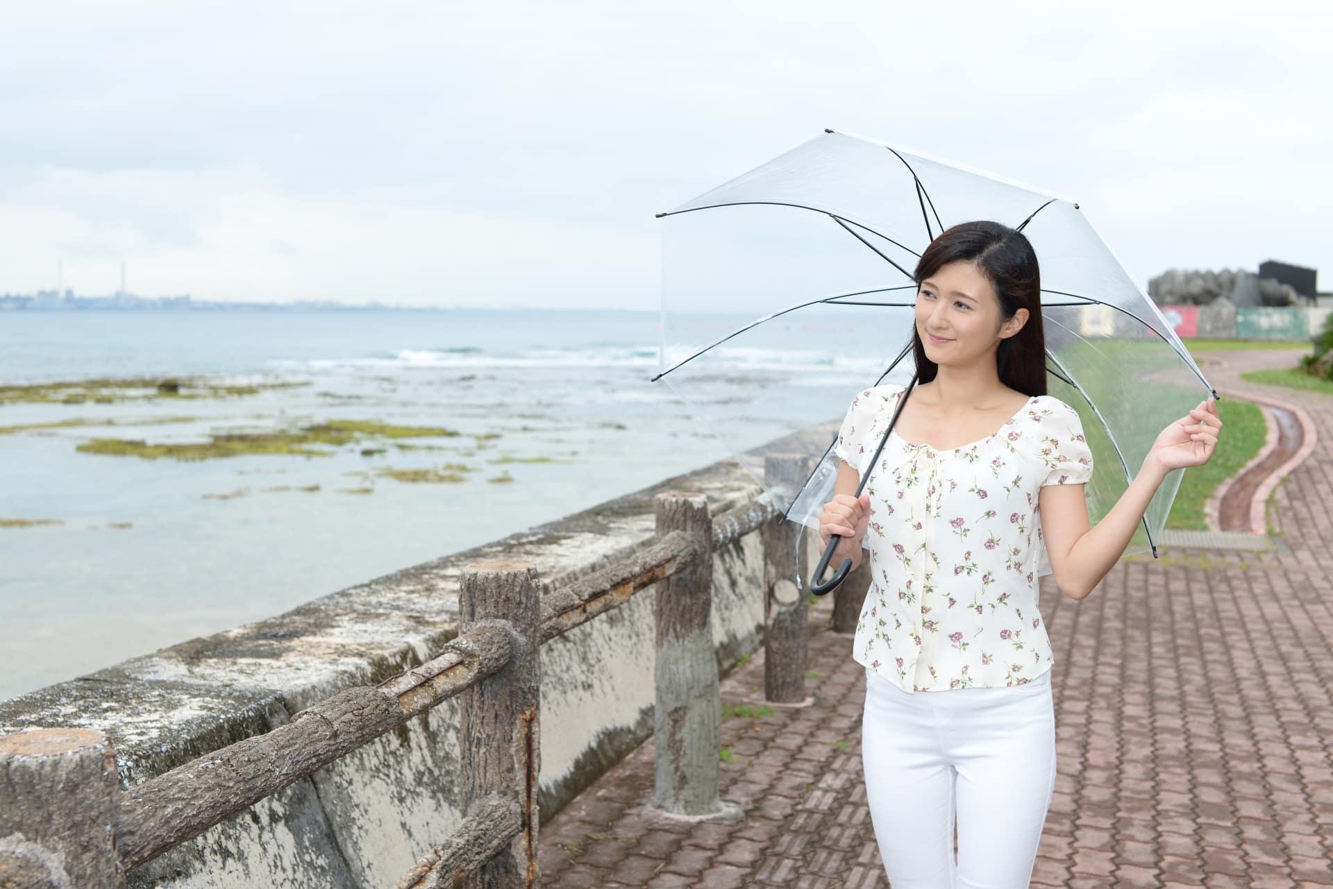 雨の海辺を歩く女性