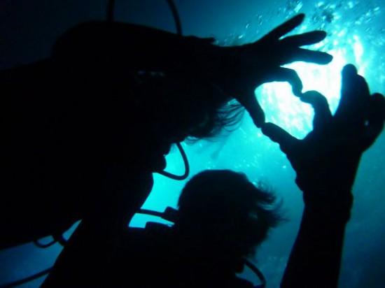 ダイビングで手でハートを作ったシルエット写真