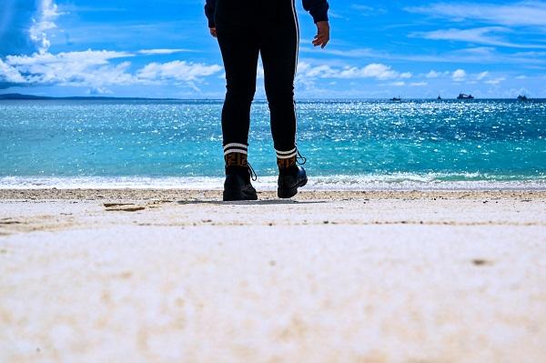 沖縄の砂浜を歩く人